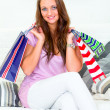Royalty-Free Stock Photo: Smiling pretty woman sitting on sofa and holding shopping bags in hands