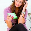 Attractive woman sitting on couch and listening music in headphones - Photo