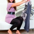 Pretty woman sitting on sofa and holding hangers with clothes in hands — Stock Photo