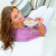 Smiling young woman sitting on sofa and eating muesli — Stock Photo