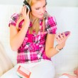 Happy young female sitting on sofa and listening music in headph — Stock Photo