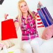 Smiling pretty woman sitting on divan and holding shopping bags — Stock Photo