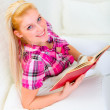 Smiling pretty woman relaxing on sofa and reading book — Stock Photo