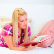 Happy young woman laying on sofa and reading book — Stock Photo