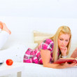 Modern housewife laying on couch and reading book — Stock Photo