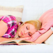 Pretty young woman sleeping on sofa with open book near head — Stock Photo