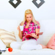 Modern housewife sitting on sofa drinking tea and reading book — Stock Photo