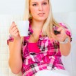 Pretty young woman sitting on couch with cup of coffee and watch — Stock Photo #8578325