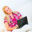 Happy young housewife sitting on divan and working on laptop — Stock Photo #8578335