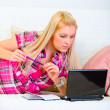 Pretty young woman laying on couch with notepad and pen and look — Stock Photo #8578354