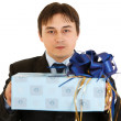 Stock Photo: Confident young businessman holding present in hands