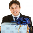 Smiling young businessman holding present in hands — Stock Photo #8578950
