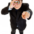 Serious businessman looking through binoculars and pointing finger at you — Stock Photo #8579407