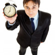 Smiling young businessman holding alarm clock in hand — Stock Photo