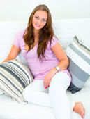 Smiling attractive young woman sitting on white sofa — Stock Photo