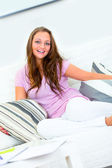 Laughing attractive young woman relaxing on white couch — Stock fotografie