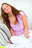 Happy pretty young woman sitting on white couch — Stock Photo