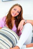 白い divan にリラックスした笑顔の美しい若い女性 — ストック写真