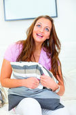 Cheerful pretty woman sitting on white sofa — Stock Photo
