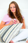 Pensive pretty woman relaxing on sofa with cup of coffee — Stock Photo