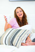Laughing pretty woman relaxing on sofa with cup of coffee — ストック写真