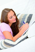 Pensive pretty woman lying on sofa and writing in notebook — Stock Photo