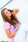 Smiling pretty woman sitting on sofa and talking on phone — Stock Photo