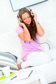 Mooie vrouw ontspannen op de sofa en luisteren muziek in hoofdtelefoon — Stockfoto