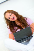 Happy pretty woman sitting on sofa and using laptop — Stock Photo