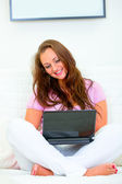 Smiling beautiful housewife sitting on sofa and using laptop — Stock Photo