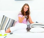 Attractive woman relaxing on sofa and watching TV — Foto de Stock