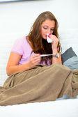 Mujer enferma con pañuelo en mano sentado en el sofá y mirando termóm — Foto de Stock