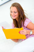 Pleased pretty woman sitting on sofa and reading letter — Stock Photo
