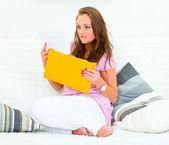 悲しい女ソファに座っていると悪いニュースを読む — ストック写真