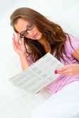 Pensive pretty woman relaxing on sofa and reading newspaper — Stock Photo