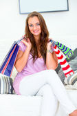 Smiling pretty woman sitting on sofa and holding shopping bags in hands — Stock Photo