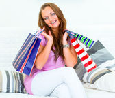 Happy pretty woman sitting on couch and holding shopping bags in hands — Stock Photo