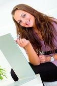 Smiling pretty woman sitting in front of mirror and applying lipstick — Stock Photo