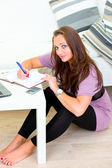 Pensive woman sitting on floor and making notes in diary — Stock Photo
