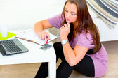 Pensive modern housewife making household budget calculations — Stock Photo