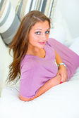 Smiling attractive young woman sitting on white couch — Stock fotografie