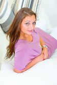Sonrisa a atractiva mujer joven sentada en el sofá blanco — Foto de Stock