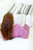 Woman sitting on sofa and reading book — Foto de Stock