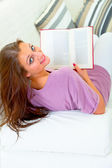 微笑着坐在白色沙发,书上有吸引力的女人 — 图库照片