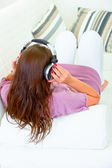 Woman sitting on sofa and listening music in headphones — Stock Photo