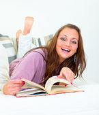 Laughing pretty woman lying on couch with book — Stock Photo