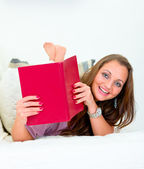Smiling attractive woman lying on sofa and peeping out from book — Stock Photo