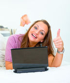 Smiling pretty woman lying on sofa with laptop and showing thumbs up gestur — Stock Photo