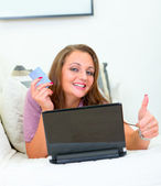 Smiling pretty woman lying on sofa with laptop and credit card and showing — Stock Photo