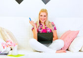Smiling pretty woman sitting on divan with laptop and credit car — Stock Photo